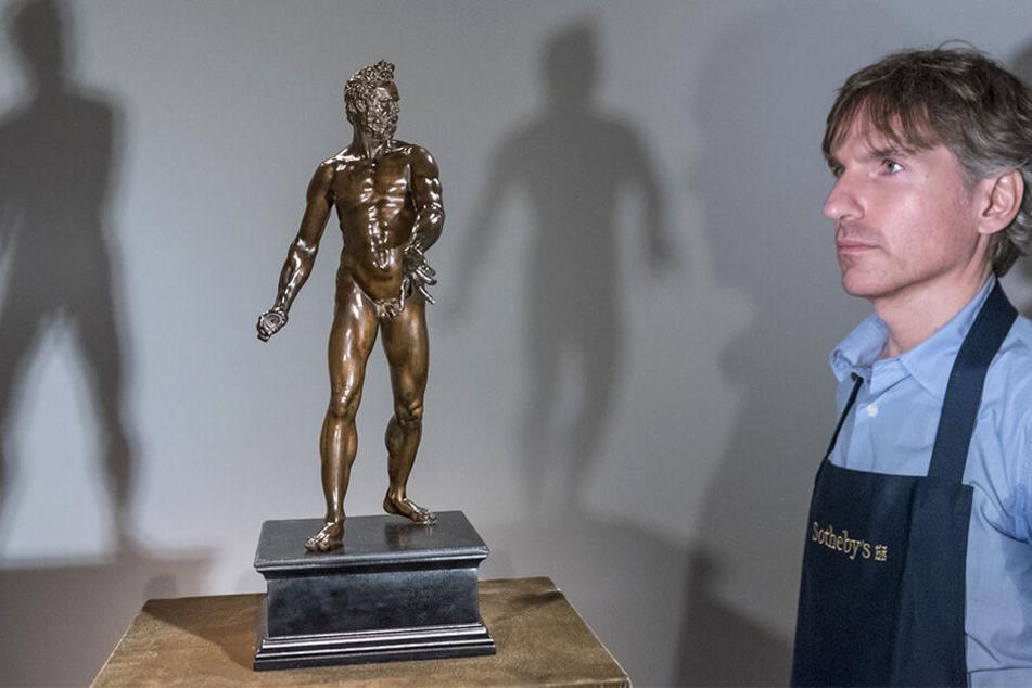 Ein Mitarbeiter des Auktionshauses Sotheby's vor der Bronze-Statuette.