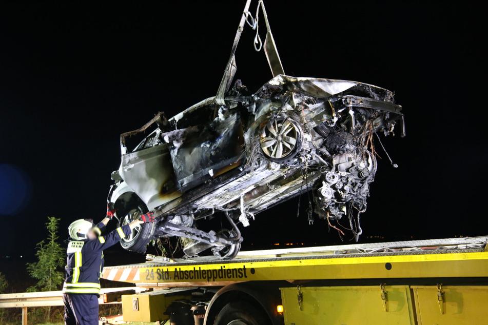 Das kaputte und verbrannte Auto wird auf die Ladefläche eines Abschleppdienstes geladen.