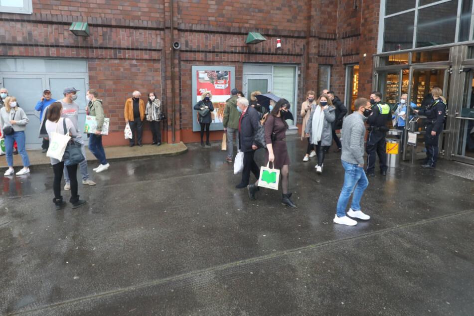 Nachdem sie aufgefordert wurden, das AEZ zu verlassen, sammeln sich Menschen vor dem Eingang.