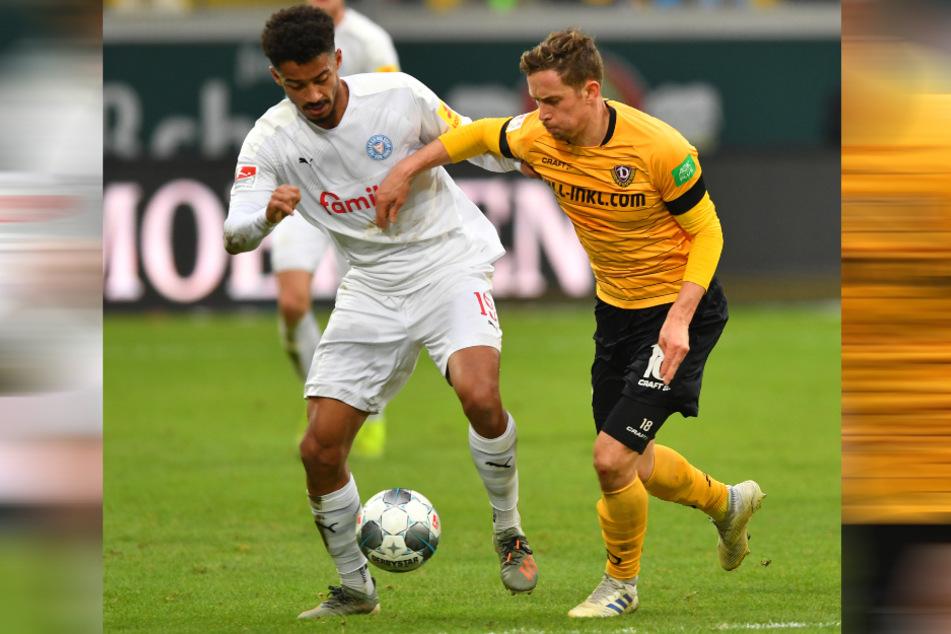 Eine Szene aus dem Hinspiel, das Kiel 2:1 gewann. Dynamos Jannik Müller (r.) und Kiels Emmanuel Iyoha duellieren sich.