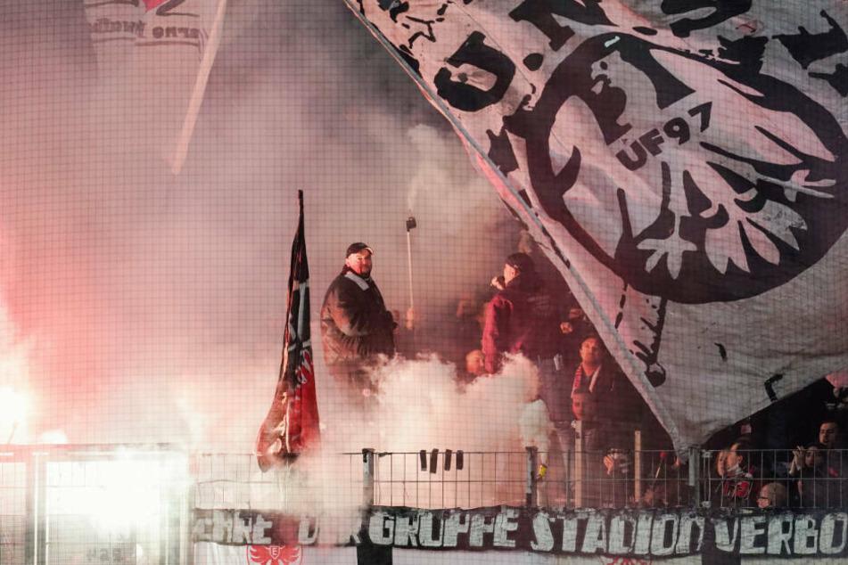 Für die Plakate werden die Vereine sicherlich nicht zur Kasse gebeten, wohl aber für das Abfackeln von Pyrotechnik. Die Eintracht-Fankurve lag vor dem Spiel in dichtem Rauch.