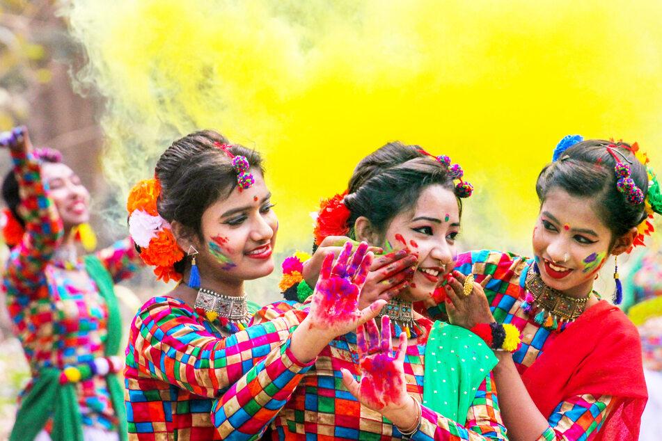 Drei Teilnehmerinnen der Feierlichkeiten zum Holi-Fest in Nadia (Indien) reiben sich gegenseitig Farbpulver in die Gesichter.