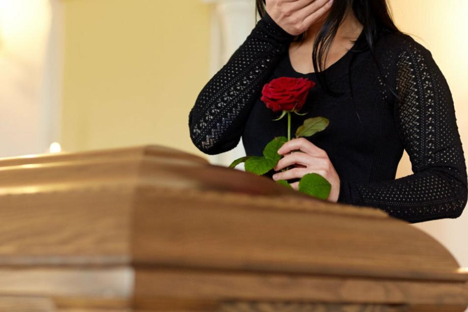 Eine Frau trauert an einem Sarg um einen Verstorbenen. (Symbolbild)