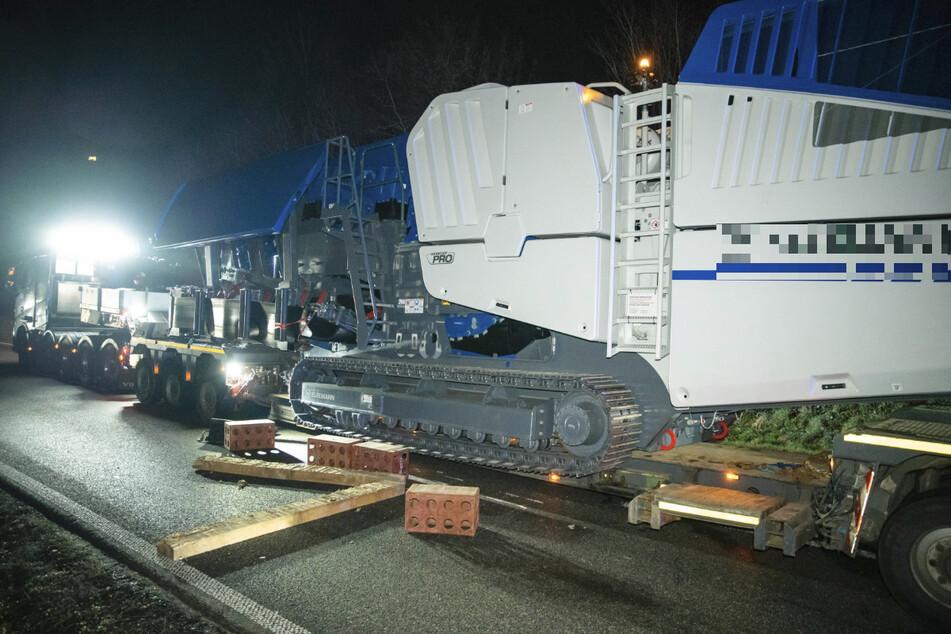 Der 76 Tonnen schwere Steinbrecher rutschte in einer Kurve von der Ladefläche des Schwertransports.