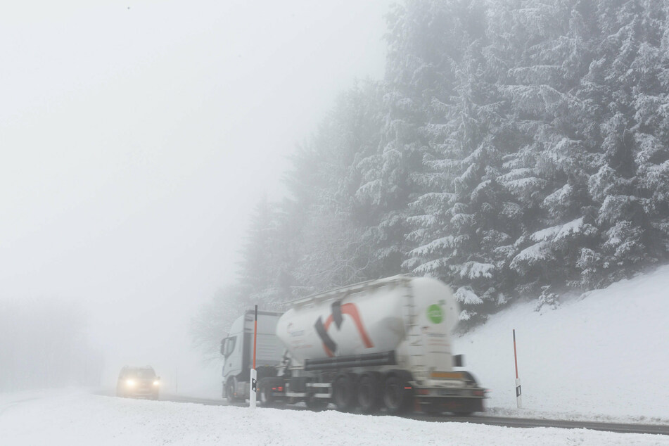 Ein LKW und ein Auto fahren im dichten Nebel auf der Landesstraße L128 im Schwarzwald durch die verschneite Landschaft.