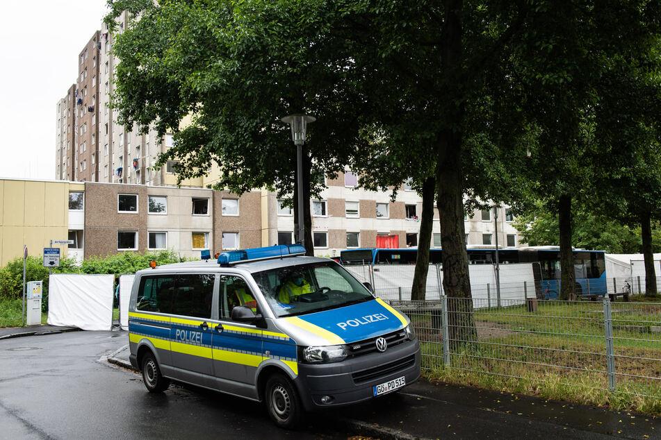 Ein Einsatzfahrzeug der Polizei steht vor einem mit Sichtschutz abgesperrten Bereich an einem Wohnkomplex in Göttingen.