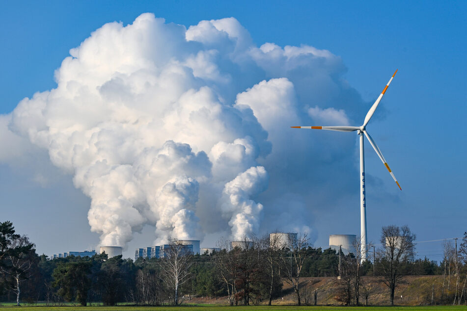 Ein Windrad steht neben den Kühltürmen eines Braunkohlekraftwerks. Die SPD strebt eine klimaneutrale Transformation deutscher Industrien an.