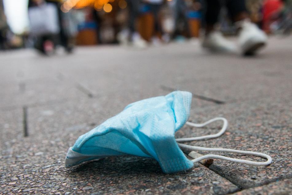 Eine medizinische Maske liegt auf dem Boden. In Thüringen hat die Zahl an Neuinfektionen mit der hochansteckenden Virus-Variante aus Indien zugenommen. (Symbolbild)
