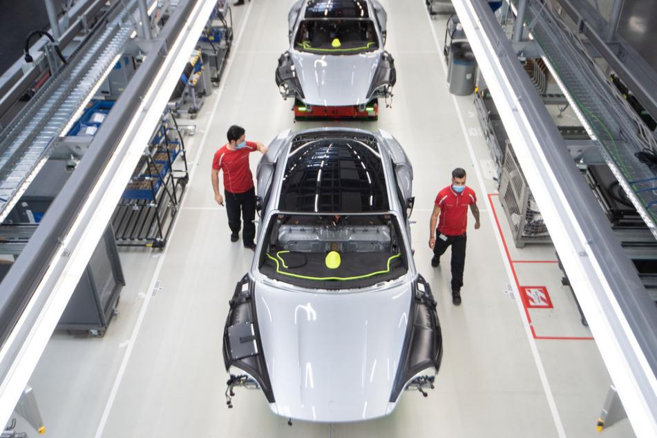 Stuttgart: Mitarbeiter der Porsche AG haben in der Produktion des batterieelektrische angetriebenen Sportwagens Porsche Taycan einen Mund-Nasen-Schutz an.