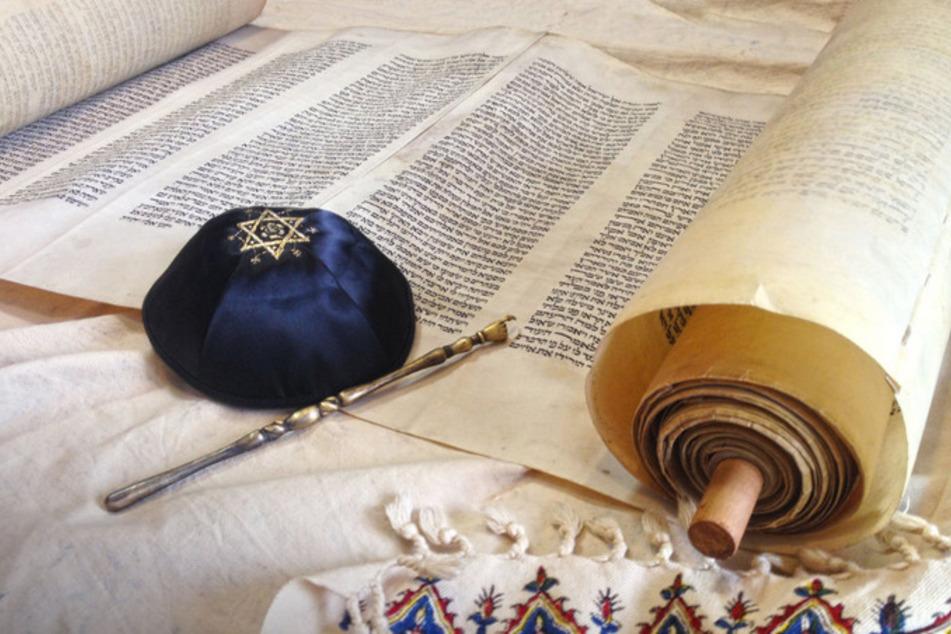Symbole des Judentums: handgeschriebene Tora, reich verzierte Kippa und silberner Jad (Foto @123RF/Oleg Ivanov).