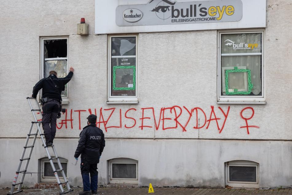 """Polizisten untersuchen das Wohnhaus mit der Kneipe """"Bulls Eye"""", in dem es zu einer Explosion gekommen war. Die Ermittler von einem politischen Hintergrund aus."""