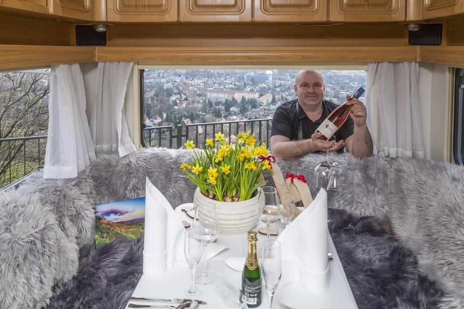 Wirt Marco Stelter (41) reicht eine Flasche Rosé in den Wohnwagen, der gemütlich eingedeckt ist.