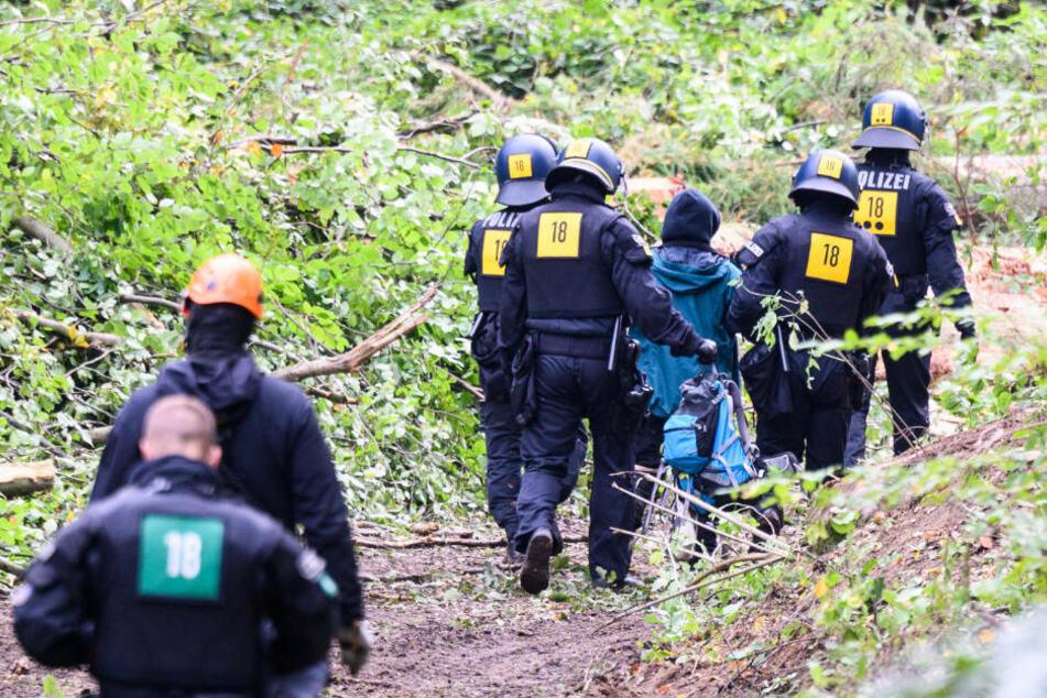 Einsatzkräfte der Polizei führen einen Aktivisten im Herrenwald aus dem Rodungsgebiet.