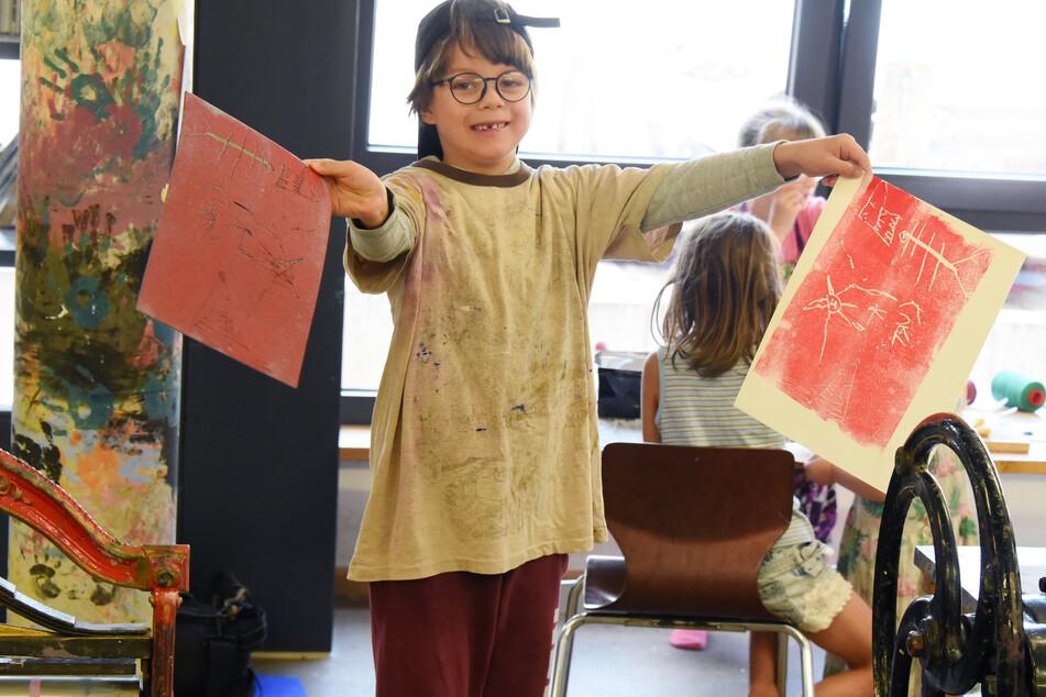 Der sechsjährige Kurt zeigt stolz seine selbstgemalten Bilder, die er an einer Druckpresse im Linoldruckverfahren gefertig hat.