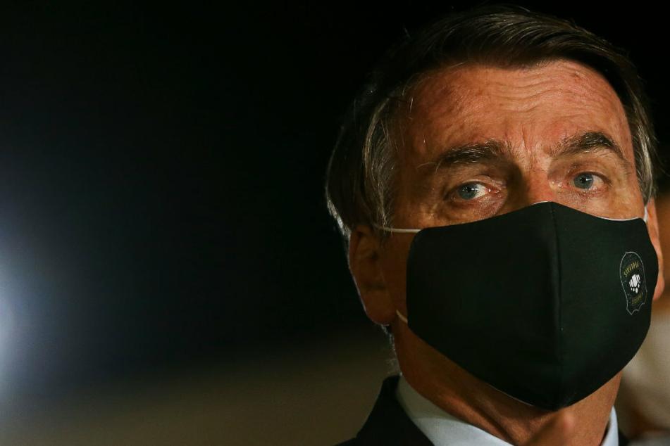 Jair Bolsonaro, Präsident von Brasilien, spricht mit schwarzem Mundschutz vor Journalisten im Regierungspalast.