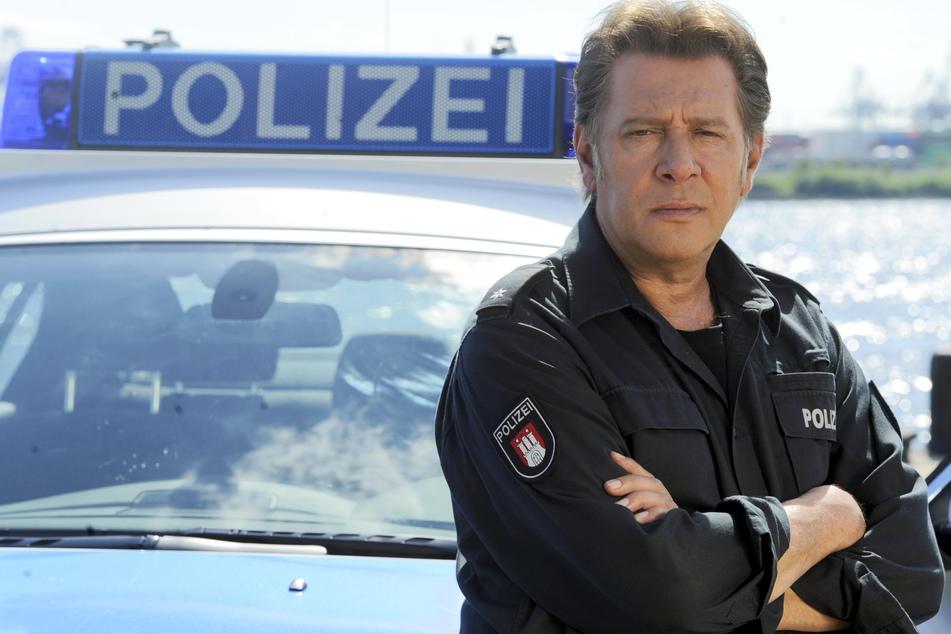 """Der Schauspieler Jan Fedder (†64) steht bei einem Fototermin zum """"Großstadtrevier"""" an einem Polizeiwagen. (Archivbild)"""