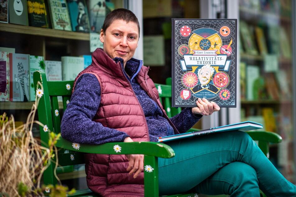 """Mica Kempe (44) zeigt vor dem """"MonOkel"""" das aufwendig gestaltete Buch """"Albert Einsteins Relativitätstheorie""""."""