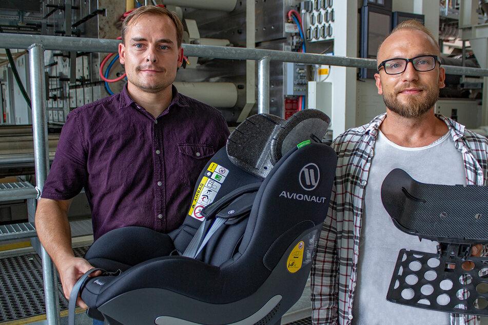 Die TU-Forscher Norbert Schramm (36, l.) und Tomasz Osiecki (33) präsentieren den Kindersitz mit der neu entwickelten Kopfstütze.