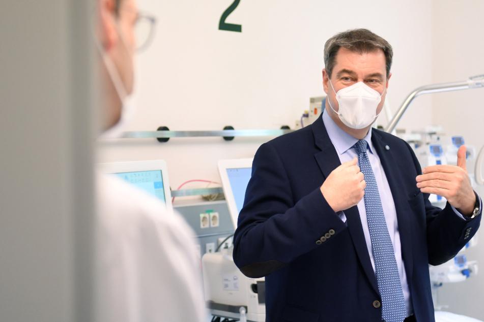 Markus Söder (CSU), bayerischer Ministerpräsident unterhält sich im Krankenhaus München Schwabing in einem Zimmer der Intensivstation mit Krankenhausmitarbeitern.