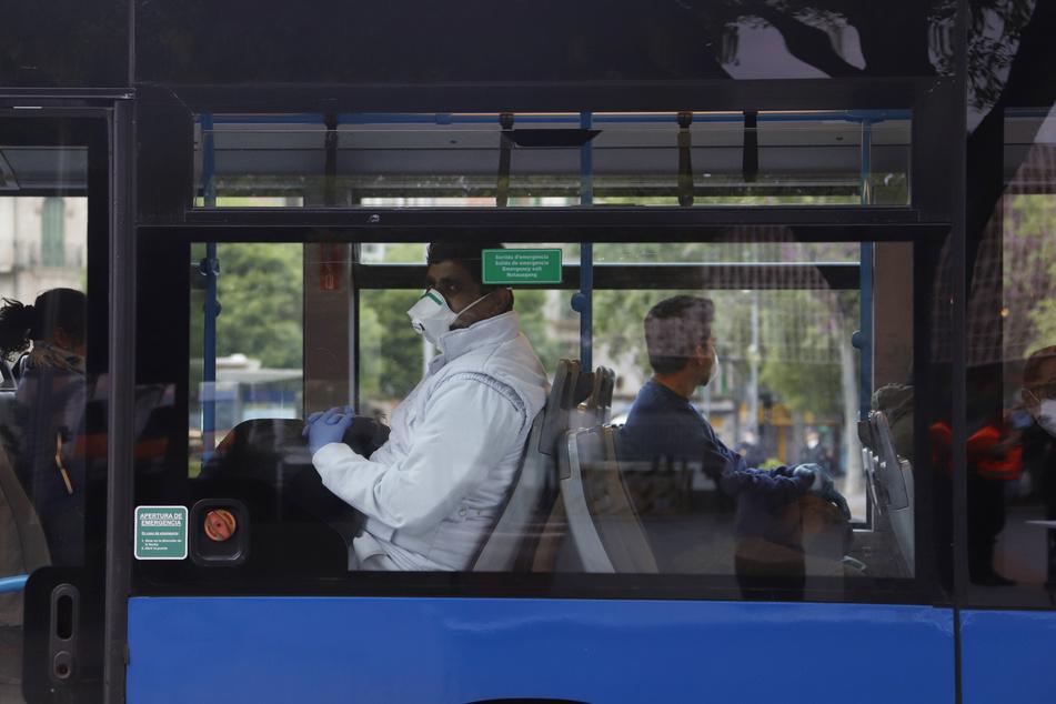 """Fahrgäste mit Mund-Nasen-Schutz sitzen am Bahnhof """"Intermodal"""" in Palma in einem Bus."""