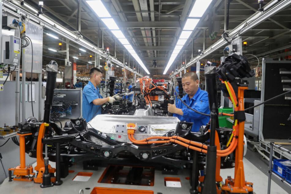 China, Shanghai: Fahrzeugbauer arbeiten in einer Werkshalle an einer Produktionslinie von SAIC Volkswagen.