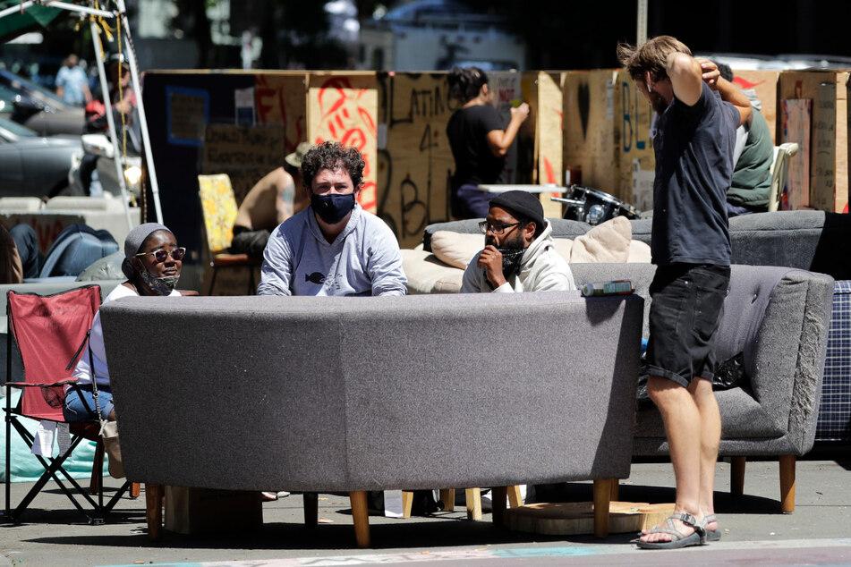 """Demonstranten sitzen auf einem Sofa in der """"autonomen Zone"""" in Seattle, die im Zuge der Proteste gegen Rassismus und Polizeigewalt entstanden ist."""