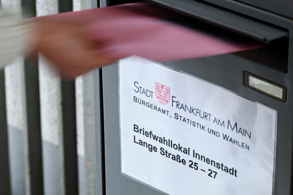 Ein Umschlag mit Briefwahlunterlagen wird am Briefwahllokal Frankfurt Innenstadt in einen Briefkasten geworfen.