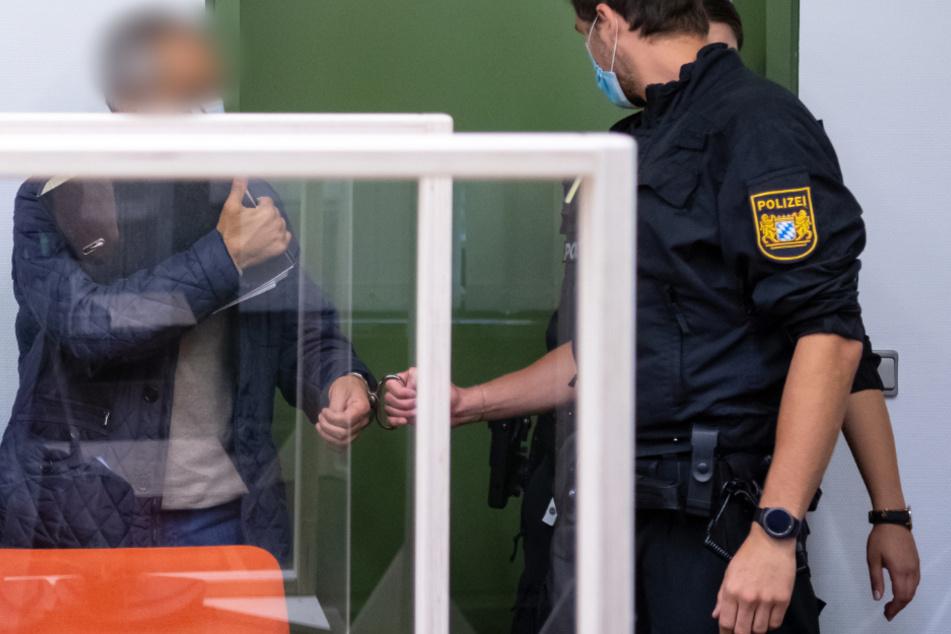 Der Angeklagte wird von Polizisten in den Gerichtssaal geführt.