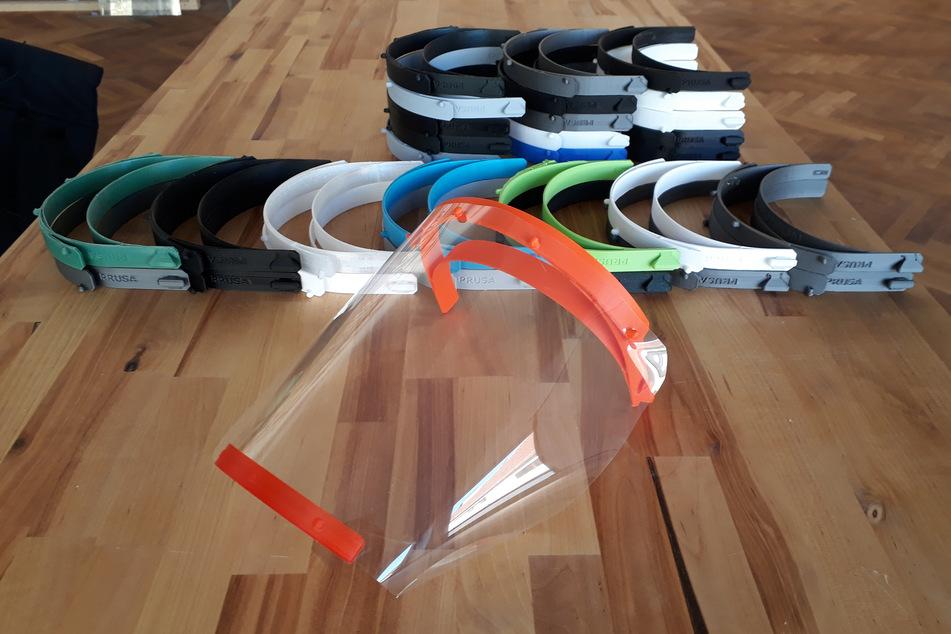 Die Bestandteile von Behelfsvisieren liegen auf einem Tisch, nachdem sie zuvor von einem 3D-Drucker erstellt wurden.
