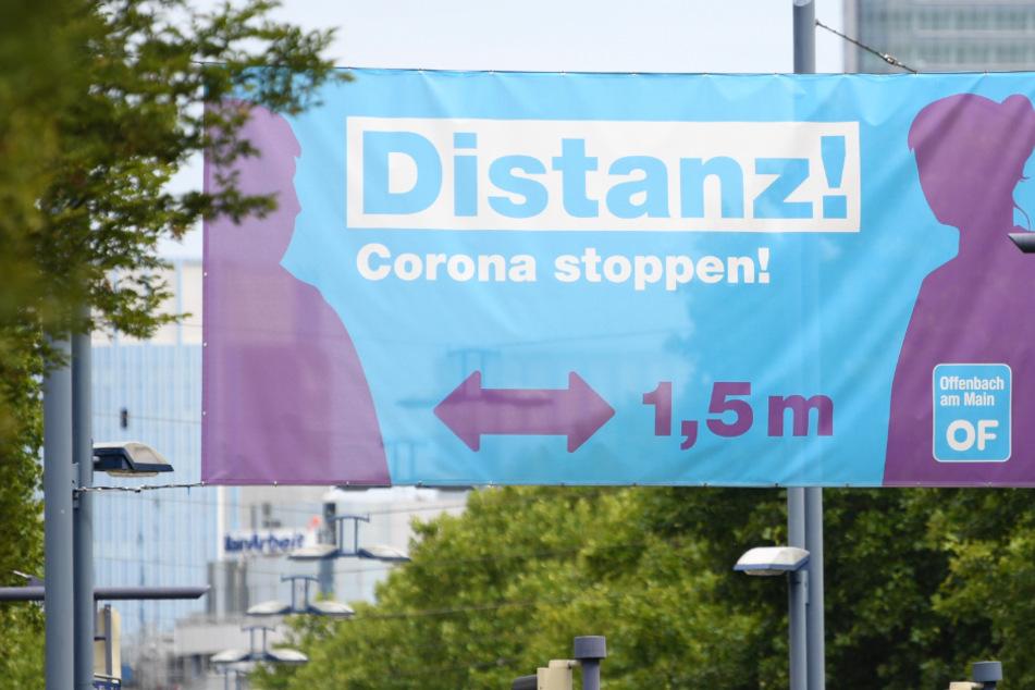 """Ein großes Plakat mit der Aufschrift """"Distanz! Corona stoppen !"""" prangt am Ortseingang von Offenbach über einer Straßenkreuzung."""