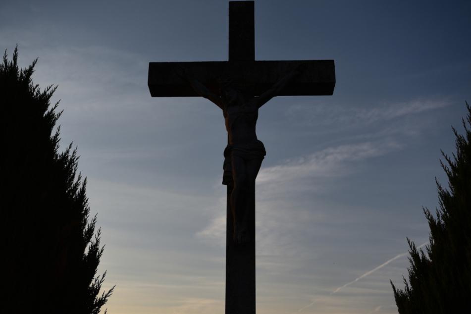 Ein katholisches Kreuz vor dem Abendhimmel. Auch die Kirche hat Schuld an einem der schwärzesten Kapitel des Landes.