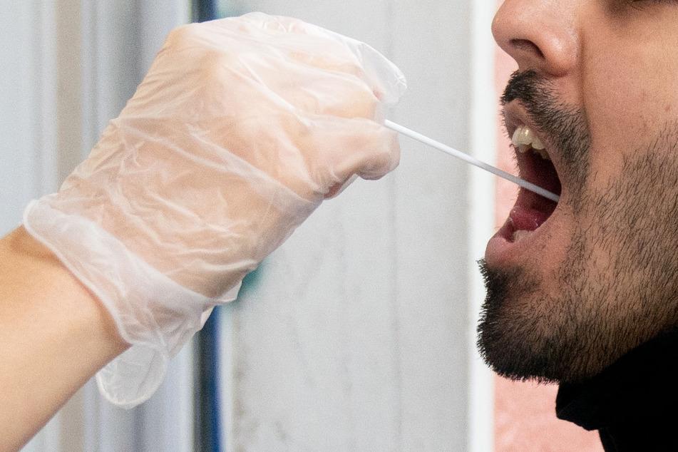 Ein Patient lässt vor einer Arztpraxis einen Abstrich für einen PCR Corona-Test machen.