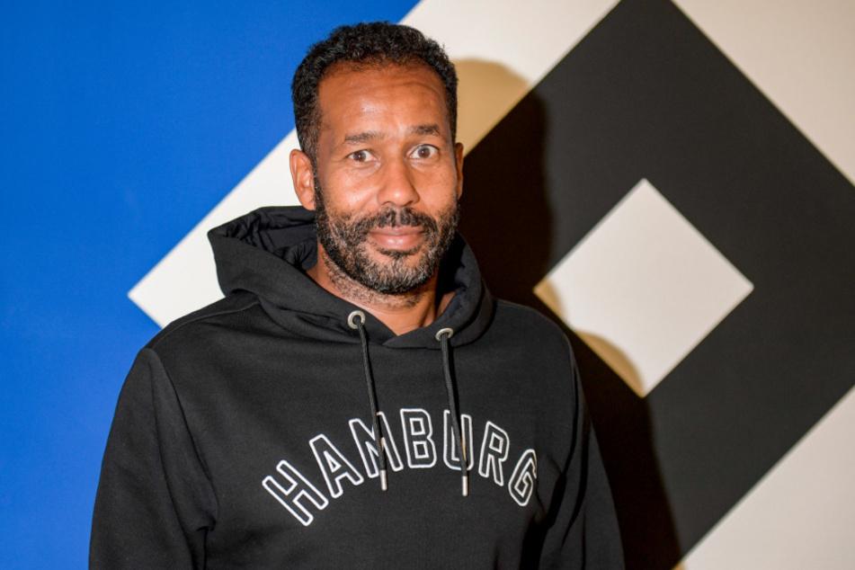 Daniel Thioune, neuer Trainer des Hamburger SV, steht vor dem Vereinslogo