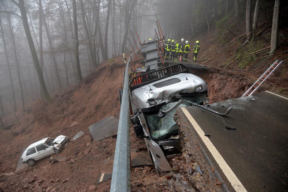 Ein Auto ist einen Hang bei Kordel hinuntergerutscht, nachdem das Auto und der Lastwagen beim Befahren der Landstraße eingebrochen sind.