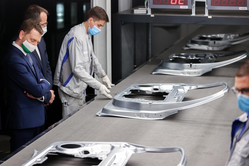 Michael Kretschmer (45, CDU), Ministerpräsident von Sachsen, steht zwischen VW-Mitarbeitern, die Türen nach dem Verlassen der neuen XL-Presse kontrollieren.