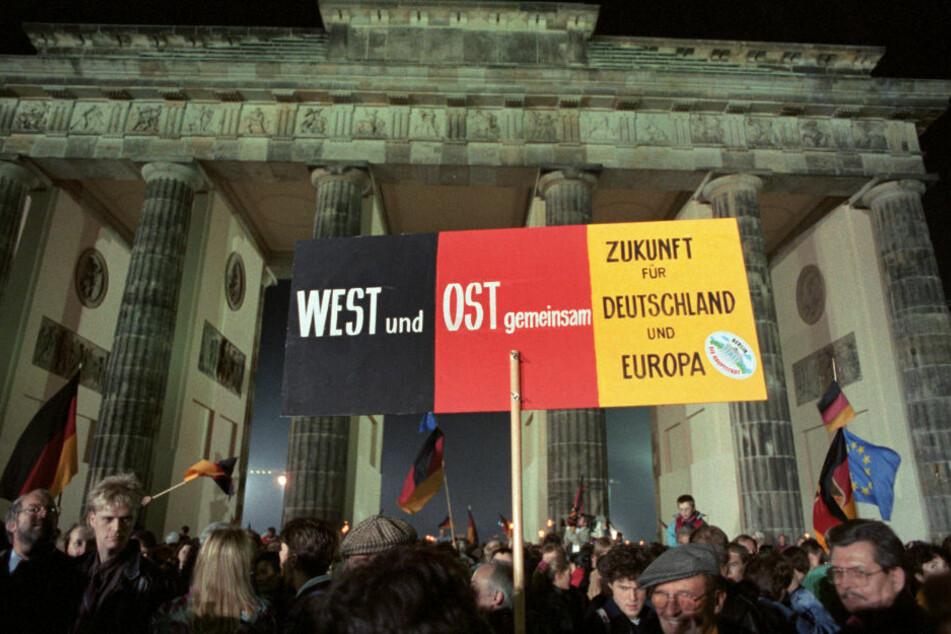 Rund eine Million Menschen feiern in der Nacht des 3.10.1990 in Berlin die wiedergewonnene deutsche Einheit. 30 Jahre später sieht die Regierung noch immer große Unterschiede zwischen Ost und West. (Archivbild)