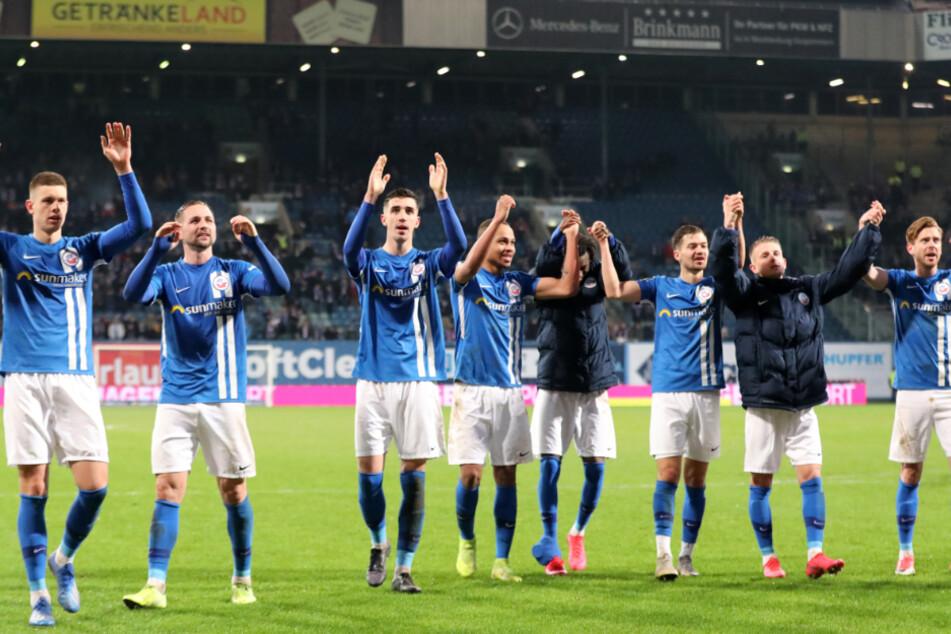 Spieler von Hansa Rostock bejubeln ihren Sieg mit den Fans nach dem Schlusspfiff im Ostseestadion.