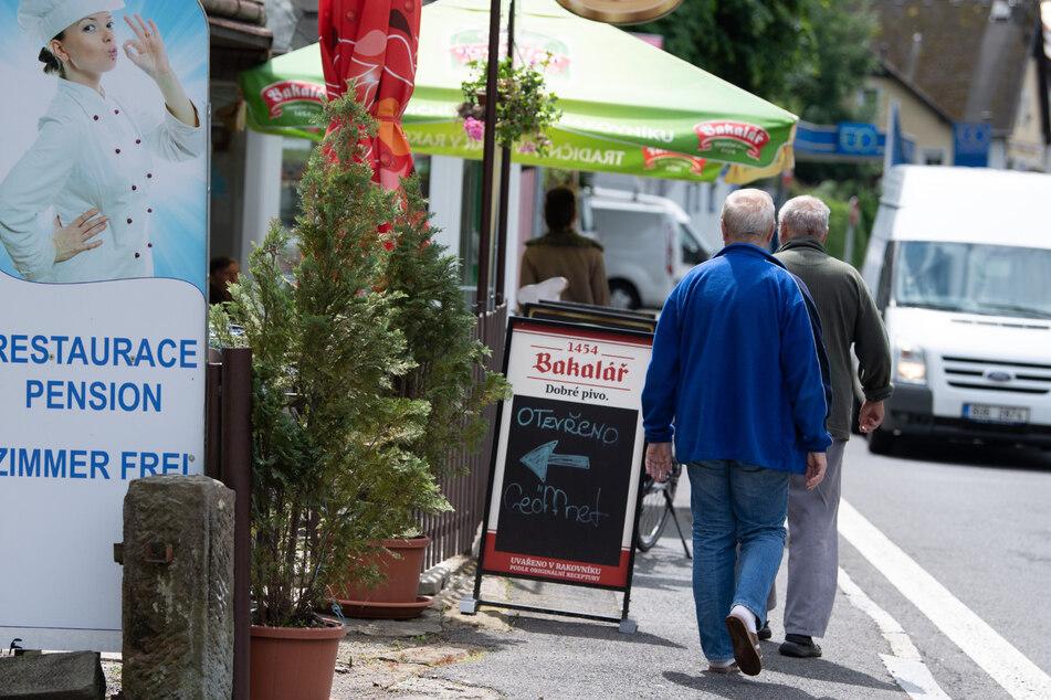 Tschechien, Hrensko: Passanten gehen auf einer Straße an einem Restaurant vorbei.
