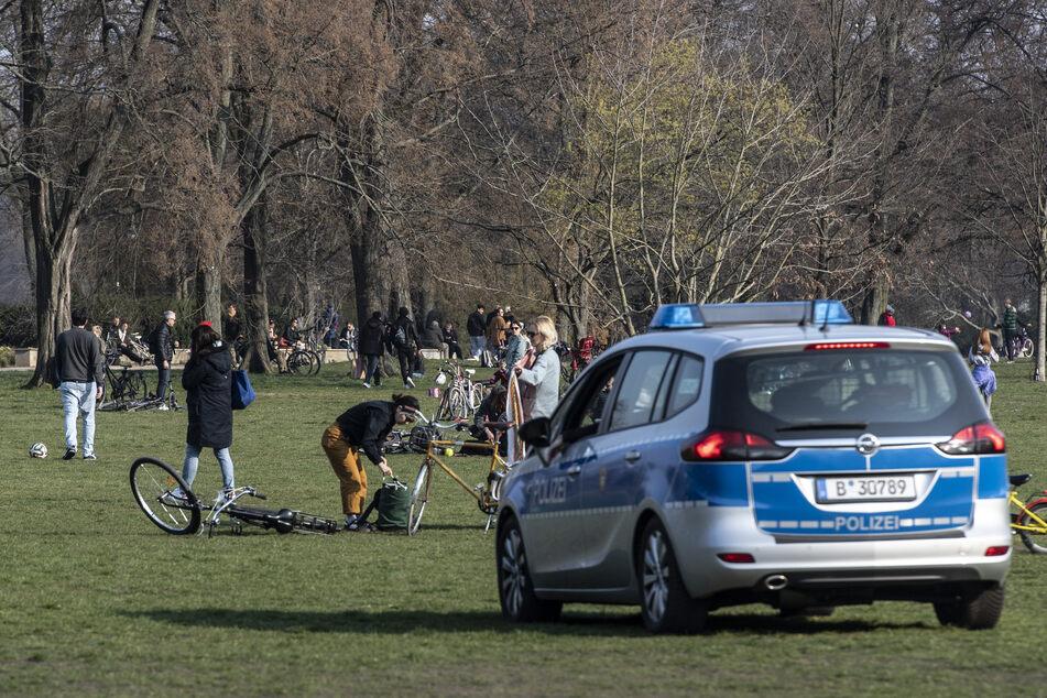 Eine Polizeistreife fährt durch den Treptower Park in Berlin und fordert die Menschen auf, die Wiese zu verlassen. Aufgrund des Coranavirus ist es verboten, sich länger in Parks und Grünauflagen aufzuhalten, ohne sich zu bewegen.