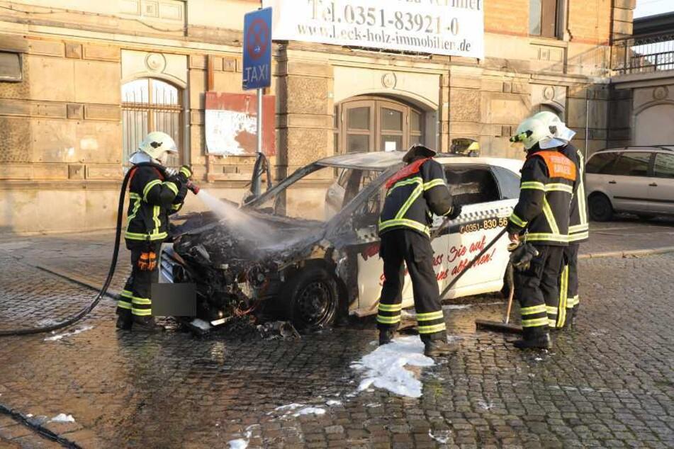 Feuerwehrleute löschen das völlig zerstörte Taxi.
