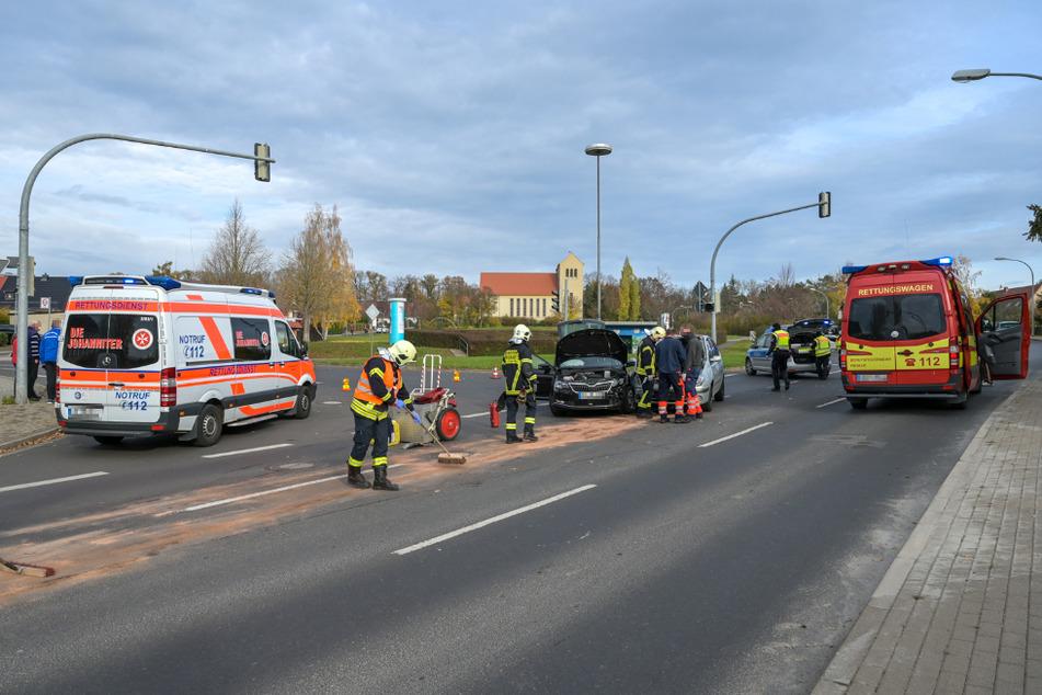 Die Feuerwehr säubert die Straße. Dahinter stehen die beiden Autos stehen nebeneinander.