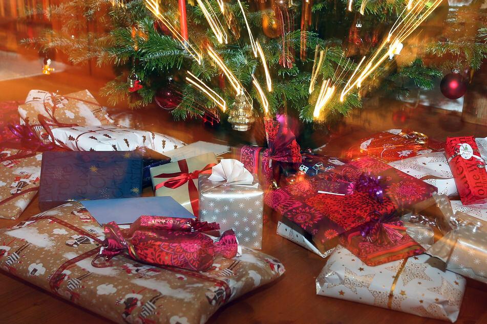 Verpackte Weihnachtsgeschenke liegen unter einem Christbaum. (Symbolbild)