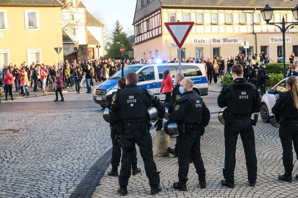Polizisten beobachten eine nicht angemeldete Versammlung von Gegnern der Corona-Maßnahmen. Daran haben in Zwönitz (Erzgebirgskreis) rund 350 Menschen teilgenommen.