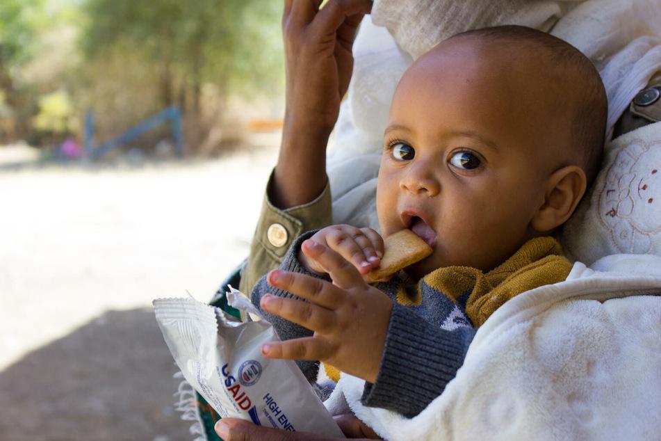 Ein sieben Monate altes Kind erhält im Februar 2021 Nahrungsmittel von UNICEF.