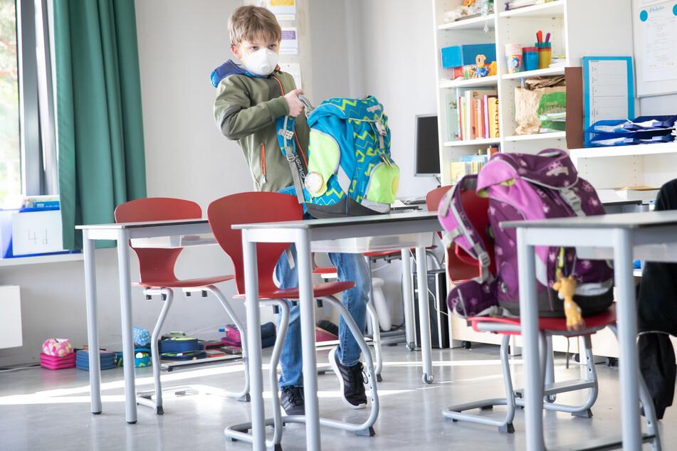 Ein Schüler kommt mit Mundschutz in ein Klassenzimmer.