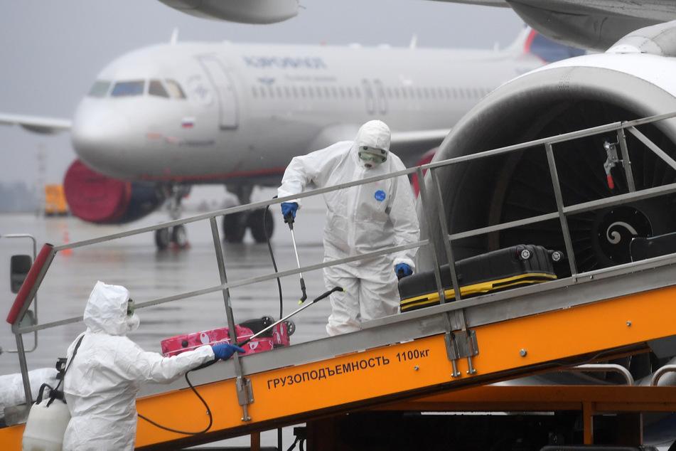 """Mitarbeiter von """"Rospotrebnadzor"""", der russischen Aufsichtsbehörde für Konsumenten- und Gesundheitsschutz, desinfizieren in Schutzkleidung das Gepäck ankommender Passagiere auf dem Flughafen Kasan."""