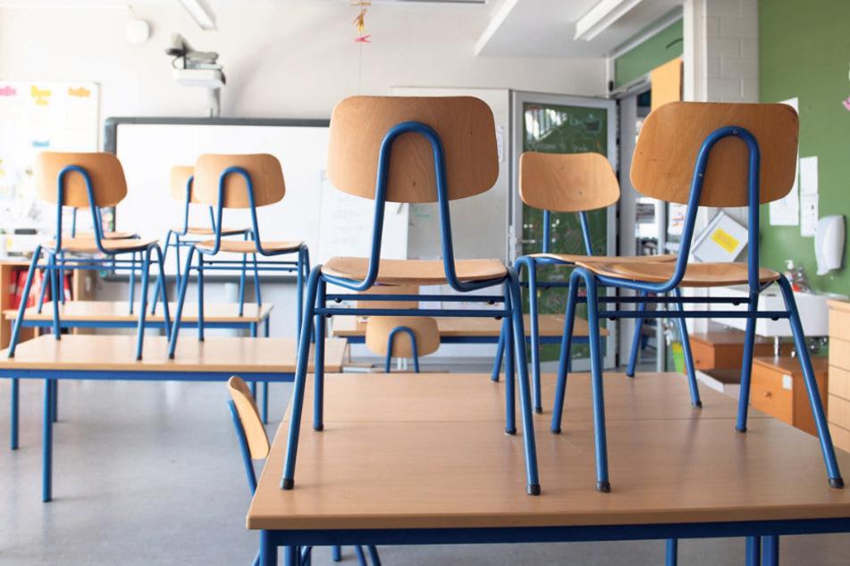 Stühle stehen in einer Schule auf den Tischen. Im Kampf gegen die Ausbreitung des neuartigen Coronavirus will der Kultusminister flächendeckende Schulschließungen nur noch in Ausnahmesituationen anordnen.