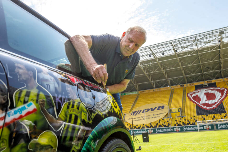 Ex-Dynamo Klaus Sammer setzt seine Unterschrift auf den Fußball-Mini.