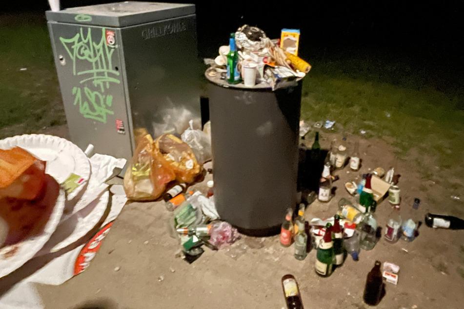Die ausgelassene Partystimmung spiegelt sich in dem Mülleimer. Verpackungen, Pappteller und reichlich Alkohol liegen im bzw. neben dem Abfallbehälter.