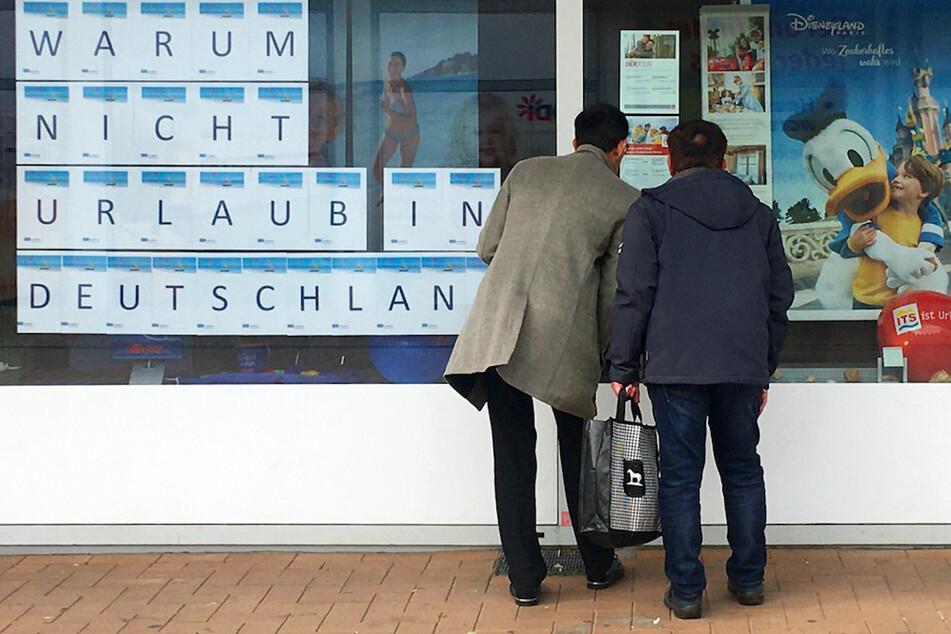 """Zwei Männer schauen in das Schaufenster eines Reisebüros, an dem mit großen Buchstaben """"Warum nicht Urlaub in Deutschland"""" zu lesen ist."""